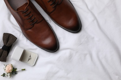 Flat lay composition with wedding shoes on white fabric, space for text