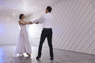 Happy newlywed couple dancing together in festive hall