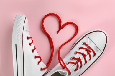 Pair of trendy sneakers on pink background, flat lay