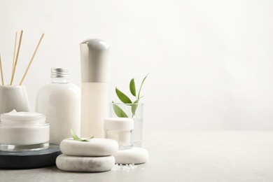 Composition with skin care products and spa stones on light background, space for text