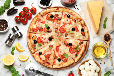 Tasty pizza with seafood and ingredients on white marble table, flat lay