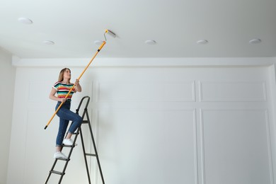 Young woman painting ceiling with white dye indoors, space for text