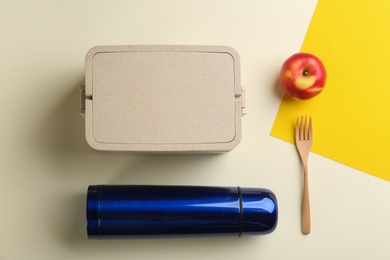 Thermos, lunch box and apple on color background, flat lay