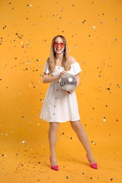 Happy young woman with disco ball and confetti on yellow background