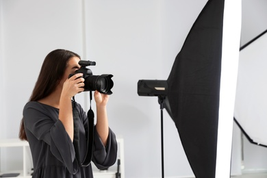 Young woman with professional camera in photo studio
