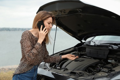 Troubled young woman talking on phone near broken car outdoors