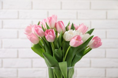 Beautiful bouquet of tulips in glass vase against white brick wall