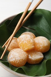 Delicious mochi served in bowl with green leaf and chopsticks on white table, closeup. Traditional Japanese dessert