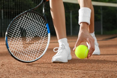 Young woman with tennis racket and ball at court on sunny day, closeup
