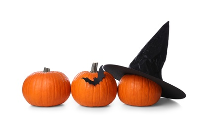 Orange pumpkins with witch hat and black paper bat isolated on white. Halloween decor