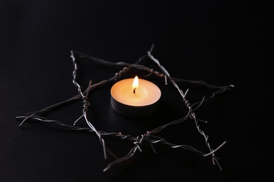 Burning candle and star of David made with barbed wire on black background. Holocaust memory day