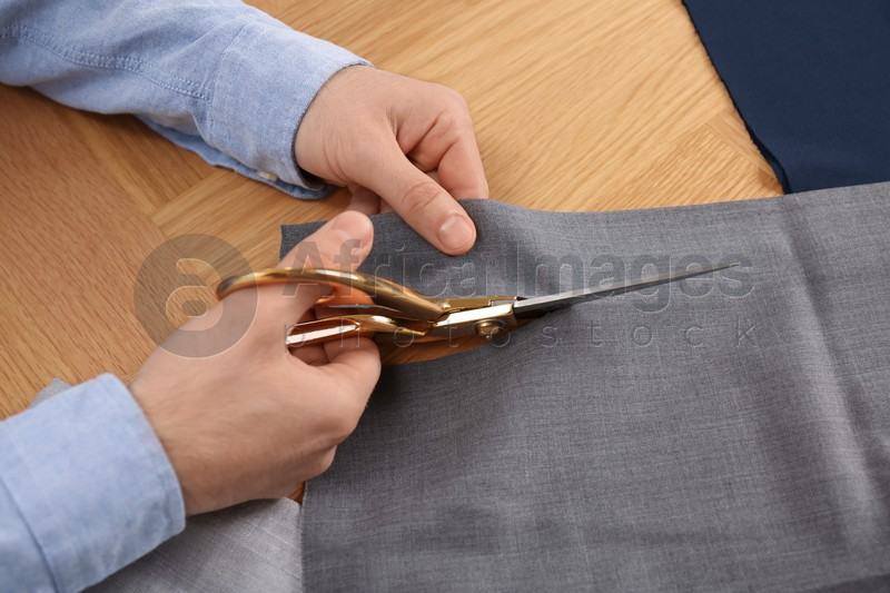 Man cutting grey fabric with scissors at wooden table, closeup