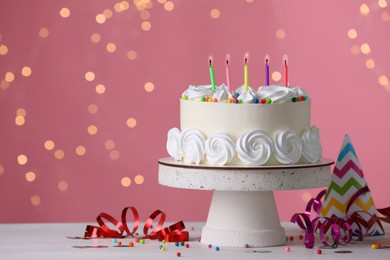 Delicious birthday cake and party decor on white wooden table against blurred festive lights, space for text