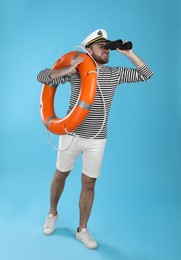 Sailor with binoculars and ring buoy on light blue background