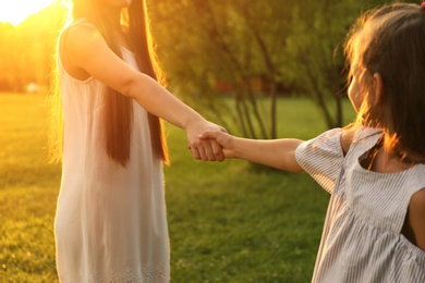 Little girl holding hands with her mother in park. Happy family