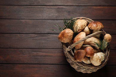 Fresh wild mushrooms in wicker basket on wooden table, top view. Space for text