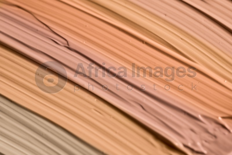 Different shades of liquid foundation as background, closeup