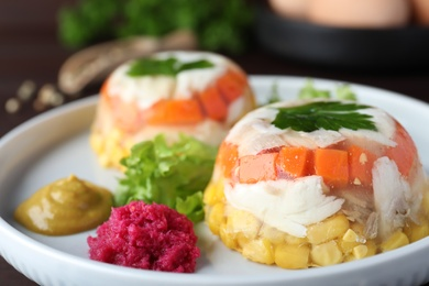 Delicious fish aspic with vegetables on plate, closeup