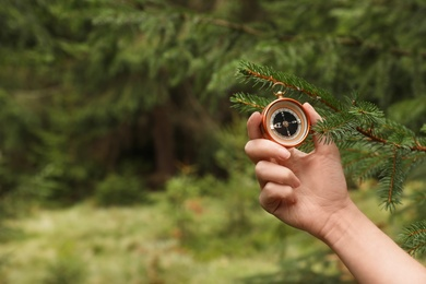 Woman checking modern compass in wilderness, closeup with space for text
