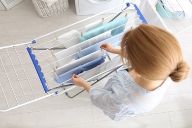 Woman hanging clean laundry on drying rack indoors, above view