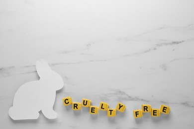 Flat lay of cubes with phrase Cruelty Free and rabbit figure on white marble table, space for text. Stop animal tests