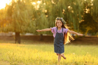 Cute little girl wearing flower wreath outdoors at sunset, space for text. Child spending time in nature