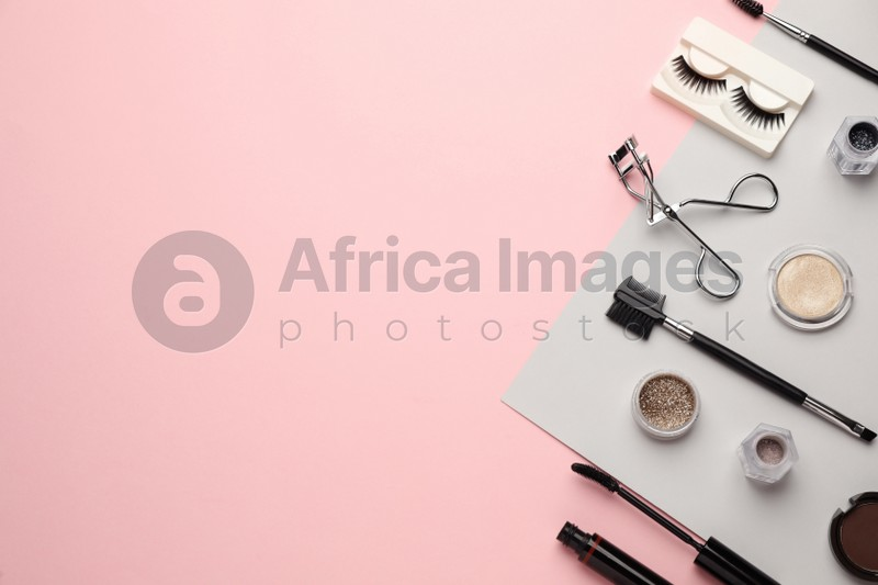 Flat lay composition with eyelash curler, makeup products and accessories on pink background. Space for text