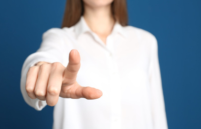Young woman against blue background, focus on hand