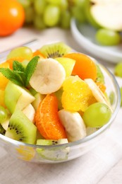 Delicious fresh fruit salad in bowl on table, closeup