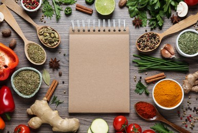 Open recipe book and different ingredients on wooden table, flat lay. Space for text