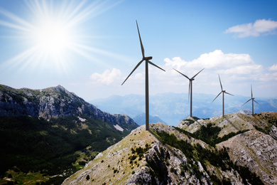 Alternative energy source. Wind turbines and mountains on sunny day