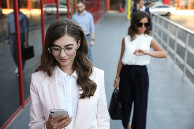Young woman with smartphone on city street