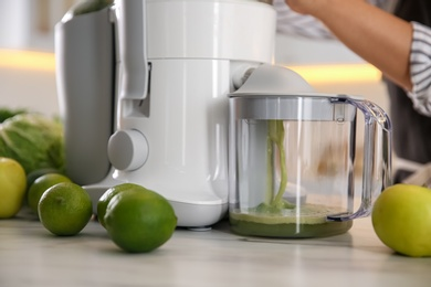 Young woman making tasty fresh juice at table in kitchen, closeup