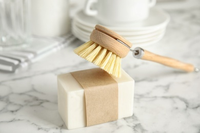 Cleaning brush and soap bar for dish washing on white marble table indoors, closeup