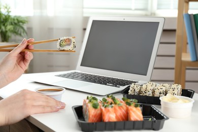 Woman having tasty sushi rolls for lunch at workplace, closeup