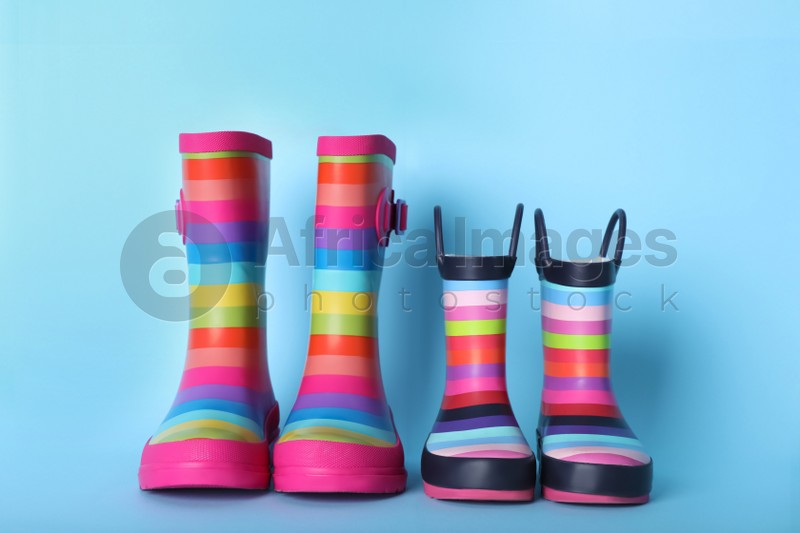Two pairs of striped rubber boots on light blue background
