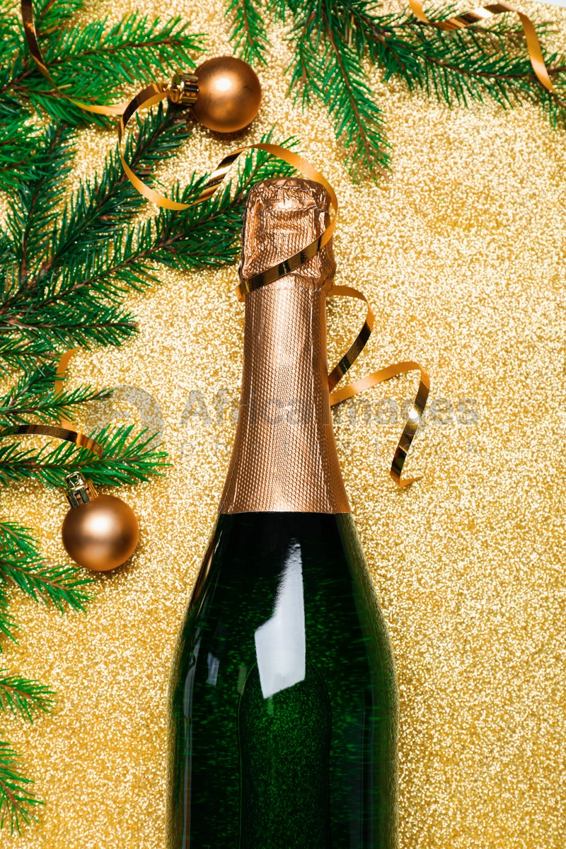 Happy New Year! Flat lay composition with bottle of sparkling wine on golden background