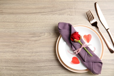 Beautiful place setting on wooden table, flat lay with space for text. Valentine's day romantic dinner