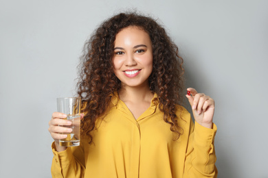 African-American woman with glass of water and vitamin capsule on light grey background