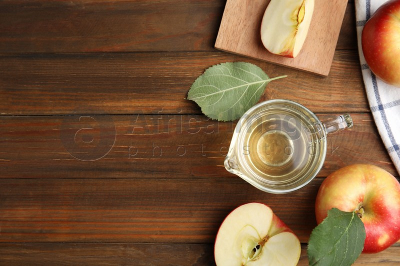 Natural apple vinegar and fresh fruits on wooden table, flat lay. Space for text