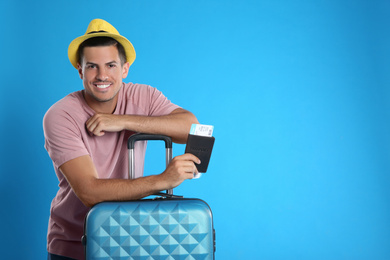 Man with suitcase and ticket in passport for summer trip on blue background. Vacation travel