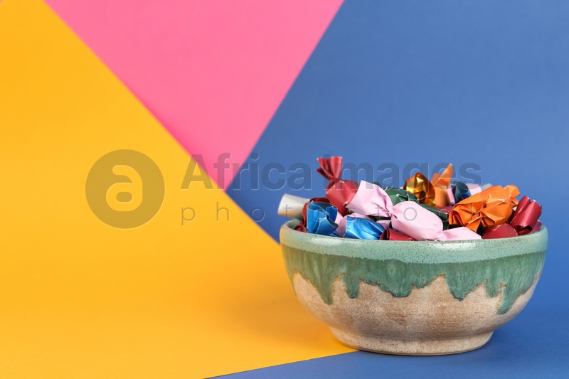 Candies in different wrappers on color background, space for text