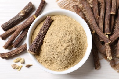 Powder in bowl and dried sticks of liquorice root on white table, flat lay