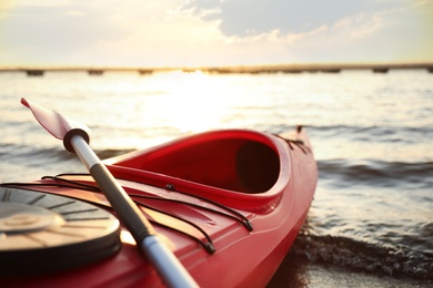 Red kayak with paddle on river at sunset, closeup. Summer camp activity