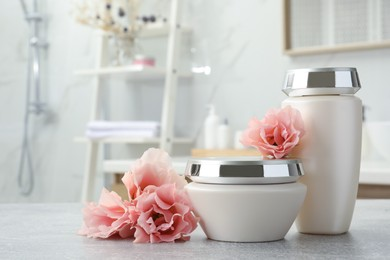 Hair care cosmetic products and beautiful flowers on light grey table in bathroom, space for text