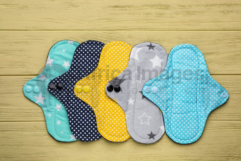 Many reusable cloth menstrual pads on yellow wooden table, flat lay