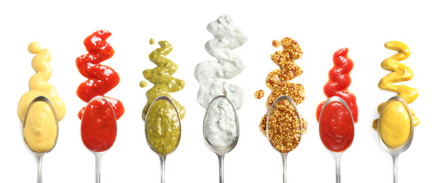 Set of spoons with different delicious sauces on white background, top view. Banner design