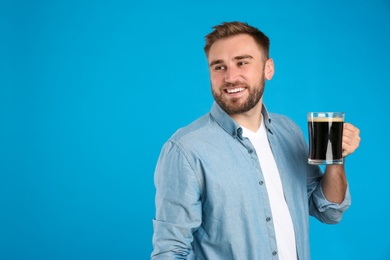 Handsome man with cold kvass on blue background. Traditional Russian summer drink
