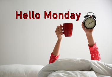 Hello Monday, start your week with good mood. Closeup view of woman with cup and alarm clock lying in bed