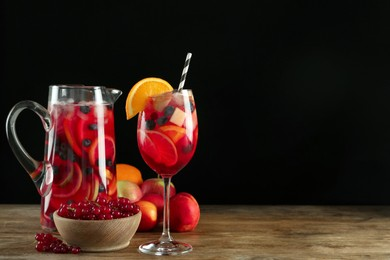 Glass and jug of Red Sangria with fruits on wooden table against black background. Space for text